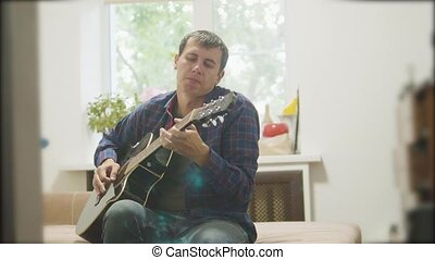 Male musician playing acoustic guitar. man playing acoustic guitar slow motion video. in the room sits lifestyle on the couch. man and guitar concept