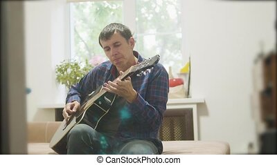 Male musician playing acoustic guitar. man playing acoustic guitar slow motion video. in the room sits on lifestyle the couch. man and guitar concept