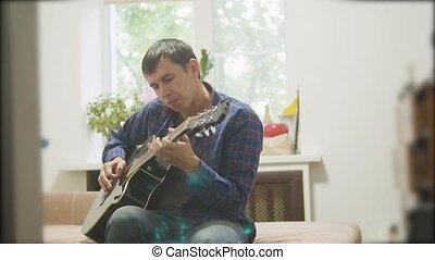 Male musician playing acoustic guitar. man playing acoustic guitar slow motion video. in the room sits on the couch. lifestyle man and guitar concept