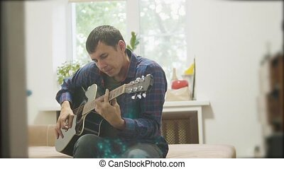 Male musician playing acoustic guitar. man playing acoustic guitar slow motion video. in the room sits on the couch. man and guitar lifestyle concept