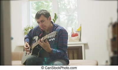 Male musician playing acoustic guitar. man playing lifestyle acoustic guitar slow motion video. in the room sits on the couch. man and guitar concept