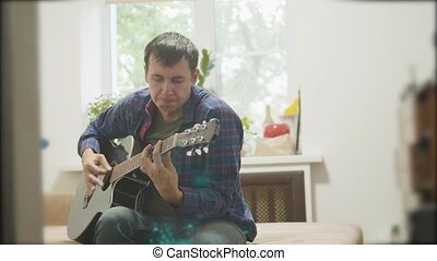 Male musician playing acoustic lifestyle guitar. man playing acoustic guitar slow motion video. in the room sits on the couch. man and guitar concept