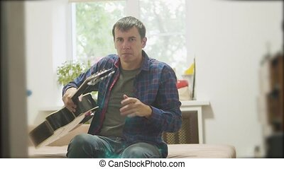 Male musician playing lifestyle acoustic guitar. man playing acoustic guitar slow motion video. in the room sits on the couch. man and guitar concept