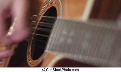 Male musician playing on acoustic guitar.