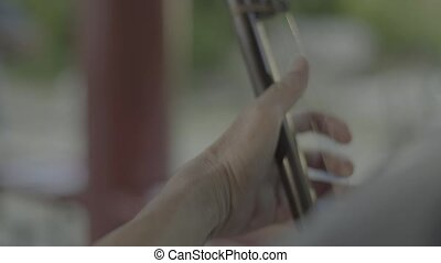 Male musician plays in the park. Beijing. China. Asia. Stock video footage UHD (4K) / 3840-2160 / MP4 / Codec H.264 / 25 fps.