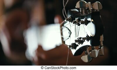 Male musician plays the guitar, hands close up, focus on the...