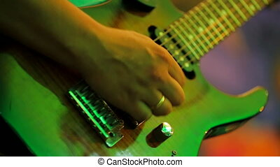 CLOSE UP: Male musician professionally playing the guitar performing at the concert in music band.