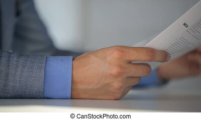 Male notary in suit jacket and light blue shirt holds a document and reads them while sitting at table, closeup.