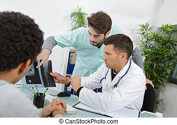 male nurse and doctor in consultation with patient