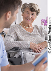 Male nurse and elder woman on a wheelchair - Male nurse...
