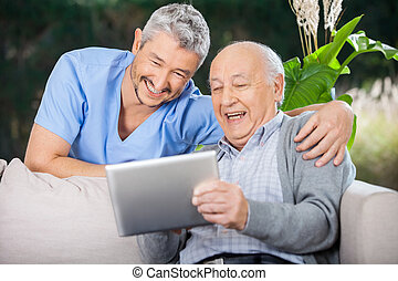 Male nurse and senior man laughing while looking at digital PC at nursing home porch