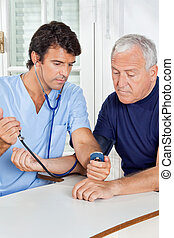 Male Nurse Checking Blood Pressure Of a Senior Man