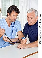 Male Nurse Checking Blood Pressure Of a Senior Man