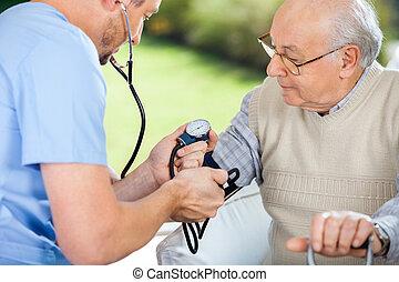 Male nurse checking blood pressure of senior man at nursing home