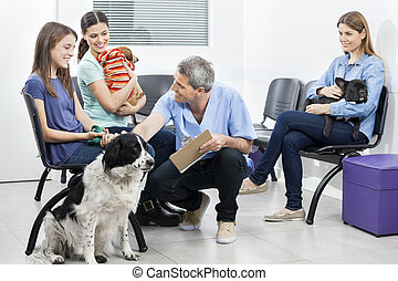 Male Nurse Crouching By Pets And Owners In Waiting Area -...