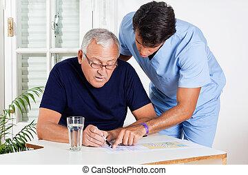 Male Nurse Helping Senior Man In Solving Puzzle