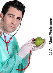 Male nurse listening to apple heartbeat