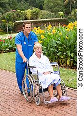 male nurse pushing patient on wheel