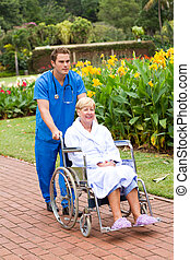 male nurse pushing patient on wheel