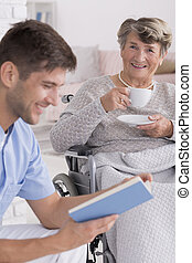 Male nurse reading a book to senior - Smiled male nurse...
