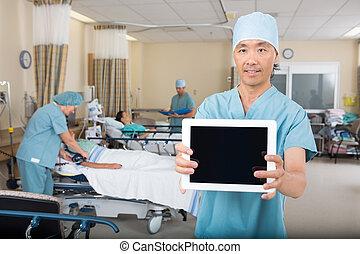 Male Nurse Showing Digital Tablet In Hospital Ward