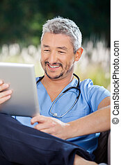 Male Nurse Smiling While Looking At Tablet Computer