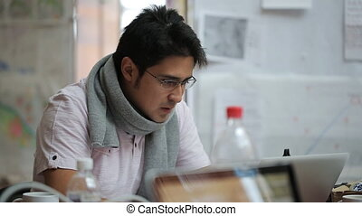 Male of Asian appearance cartographer in glasses and scarf working on the laptop.