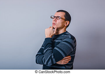 male of European appearance brunet holding hand on chin thinking