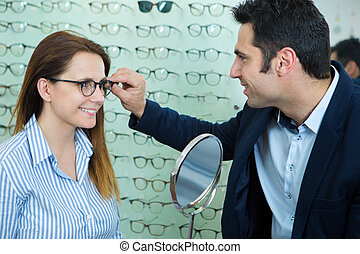male optician checking fit of glasses on female customer
