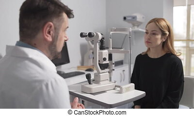 Male optometrist on consultation with patient -...