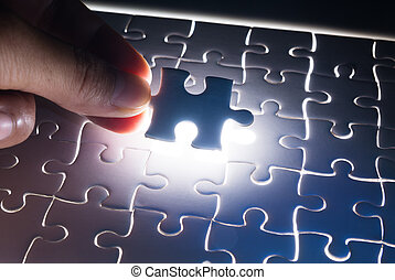 Male or Man Hand and Finger put Piece of Jigsaw in Place to Solve or Match Puzzle