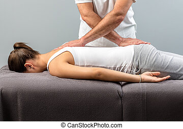 Male osteopath doing back massage on young woman.