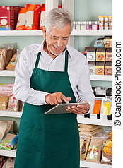 Male Owner Using Tablet In Supermarket - Happy senior male...