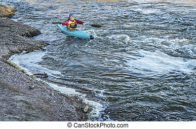 male paddler in a whitewater kayak - male kayaker is...