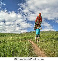 male paddler with stand up paddleboard (SUP)