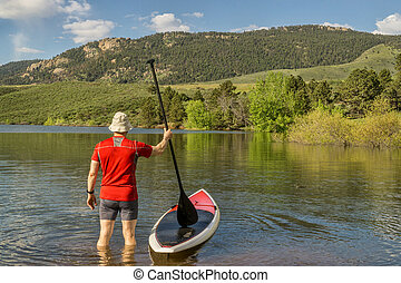 male paddler with SUP paddleboard on lake