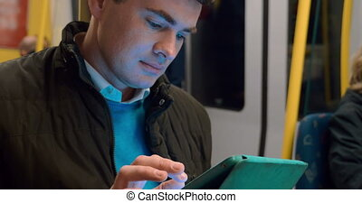 Male passenger with touch pad in subway train - Young man...