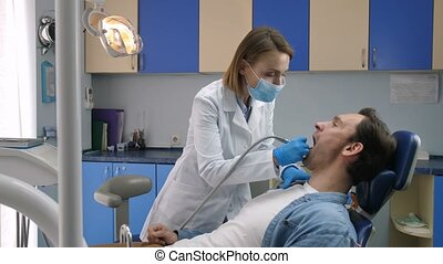 Male patient receiving tooth decay treatment - Young male...