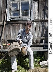 Male peasant pouring some wine in a jug