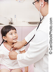 male pediatrician examining little girl