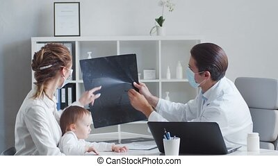 Male pediatrician is examining sick little baby. Doctor, ...