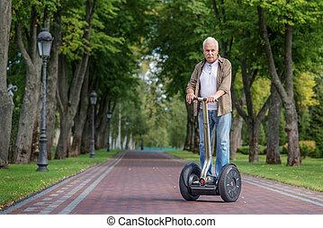 Male pensioner riding modem vehicle