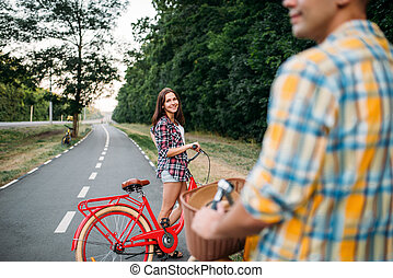 Male person and young woman riding on retro bikes