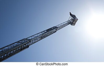 Male person in a basket on top of a high ladder, against a sunny blue sky