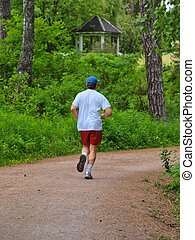 Male person running on gravel road in the forest