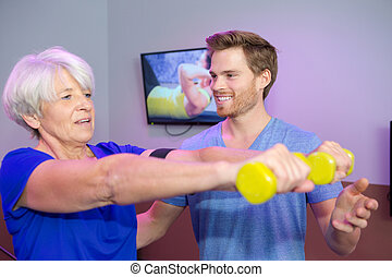 male personal trainer coaching senior woman with weights