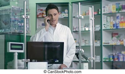 Male pharmacist communicating on phone in pharmacy