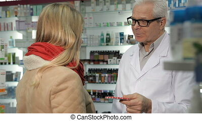 Senior male pharmacist offering pills to female customer at the drugstore. Aged caucasian man in medical uniform giving blister of pills to blond woman. Gray male druggist in glasses telling young woman about remedy