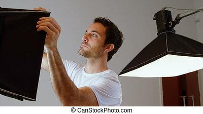 Male photographer adjusting strobe light 4k - Male...