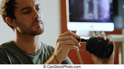 Male photographer cleaning camera lens 4k - Male...